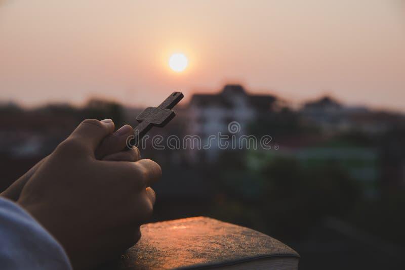 Slut upp unga händer som rymmer träkorset över den heliga bibeln och att be Kristet begrepp royaltyfria foton