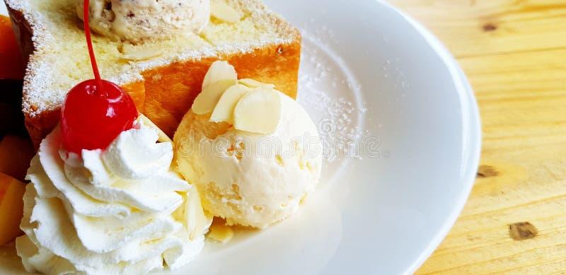 Slut upp vaniljglass, vit piskad kräm med den röda körsbäret överst och suddig bakgrund för socker för smörrostat brödstänk royaltyfri fotografi