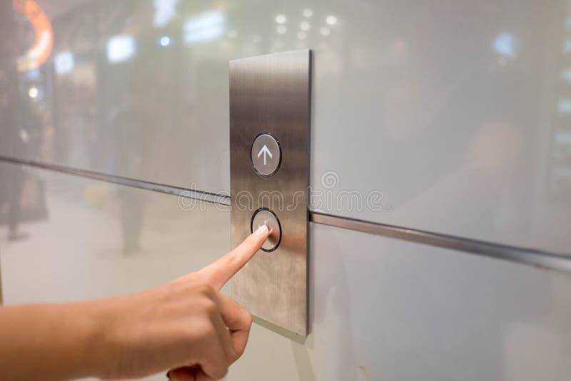 Slut upp wamanhandpress en övre knapp av hissen inom byggnaden för övrepå hög nivå golv royaltyfria bilder