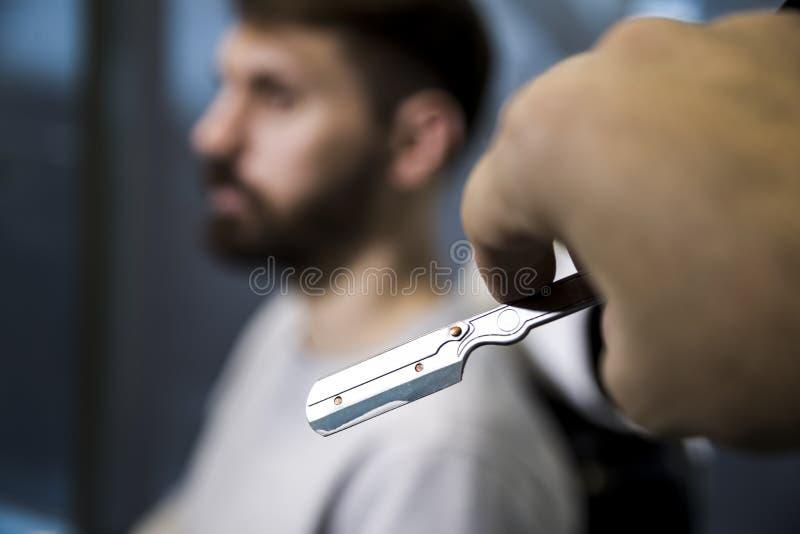 Slutet av barber's räcker upp att rymma en rakkniv och att att närma sig en skäggig klient som sitter på en stol arkivfoto