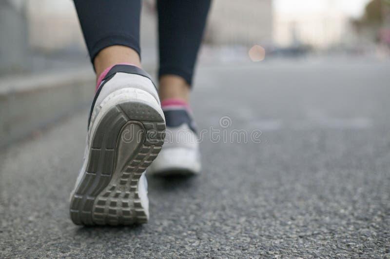 Slutet av ben i gymnastikskor går upp på vägen arkivfoton