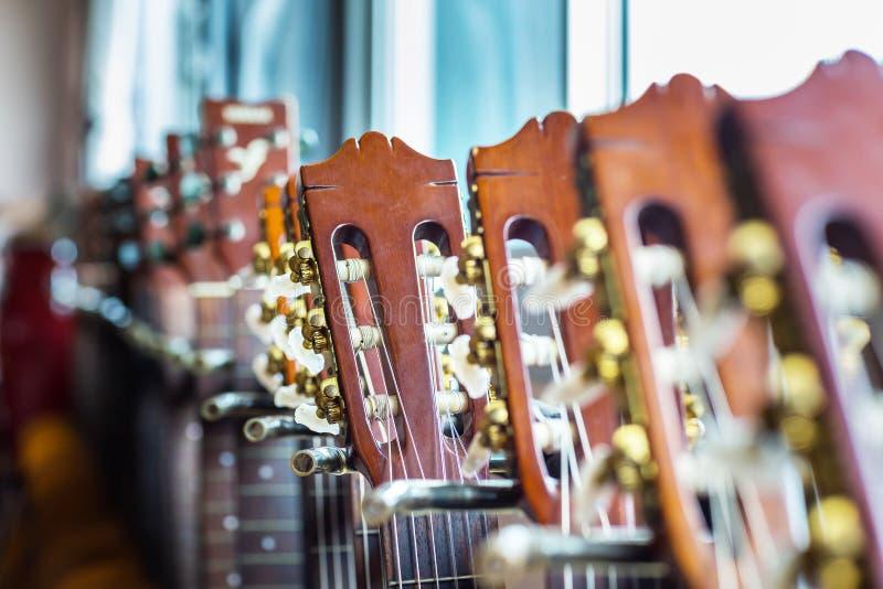 Slutet av den akustiska gitarren hånglar upp på oskarp bakgrund royaltyfri fotografi