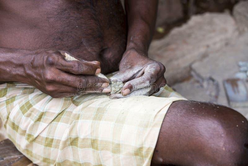 Slutet av den höga indiska asiatiska manskulptörskulptören räcker upp arbete på hans marmorskulptur med stämjärnet arkivbild