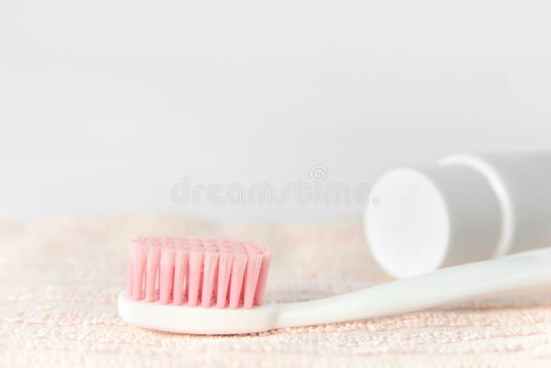 Slutet av den plast- vita tandborsten med rosa färger blir tvärarg upp och tandkräm i rör på den rosa handduken royaltyfria bilder