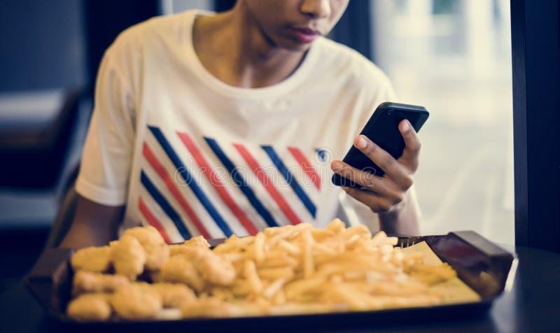 Slutet av den tonårs- pojken som använder en smartphone som äter fransman, steker upp begrepp för ungdomkultur royaltyfri bild