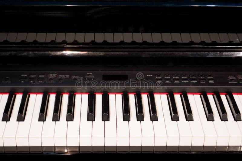 Slutet av det elektroniska pianot stämmer upp nära frontal sikt arkivfoto