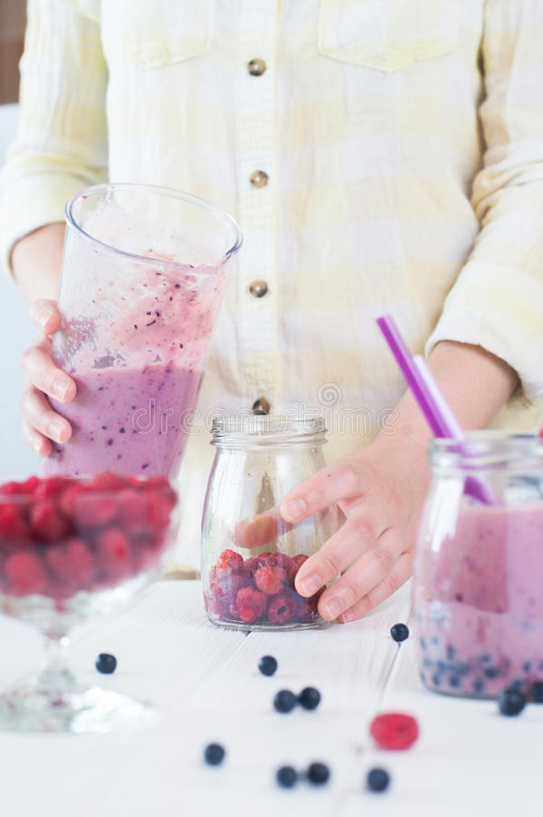 Slutet av en kvinnlig räcker upp framställning av en smoothie med frukter och ber arkivfoton