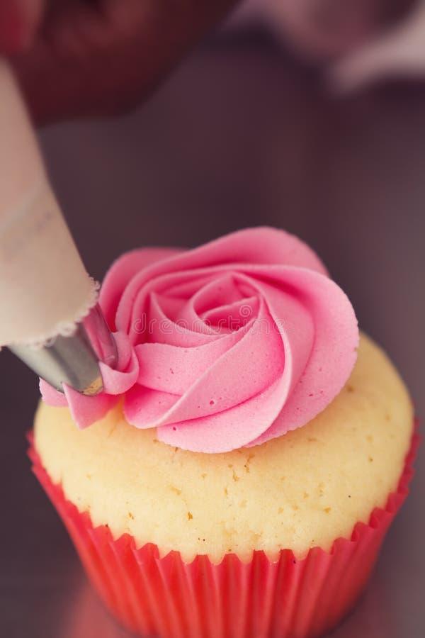 Slutet av en rosa färgros glaserade upp muffin som den är med is arkivbild
