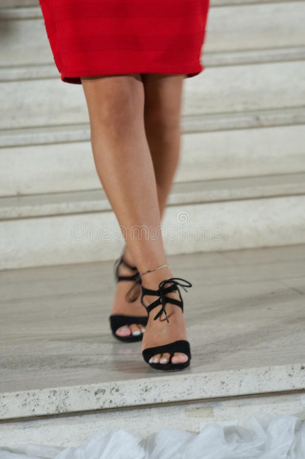 Slutet av flickan lägger benen på ryggen upp, medan gå på en stege, med svarta sandaler arkivbilder