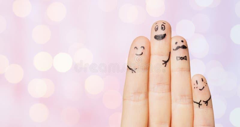 Slutet av fyra fingrar med smiley vänder mot upp royaltyfria foton