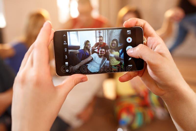 Slutet av girl's räcker upp danandefotoet med mobiltelefonen royaltyfri fotografi