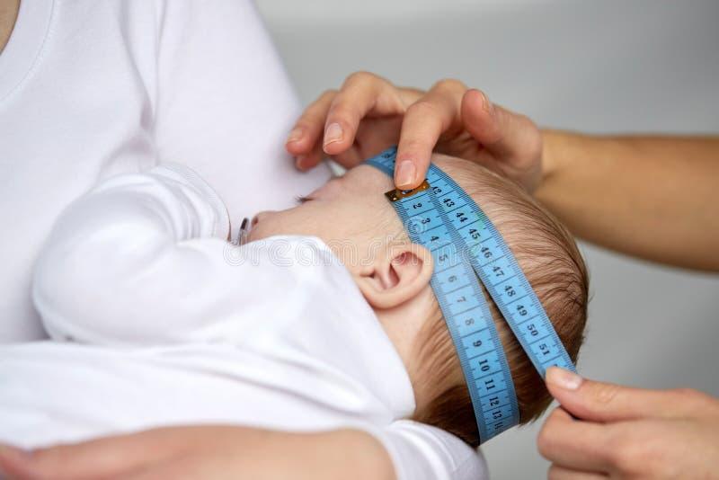 Slutet av händer med att mäta för band behandla som ett barn upp huvudet arkivfoton