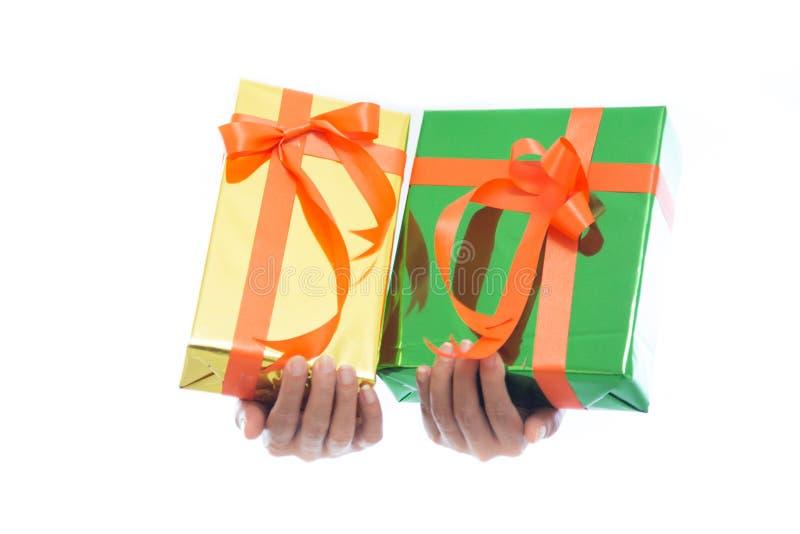 Slutet av händer rymmer upp den gröna gåvaasken isolerad på vit bakgrund royaltyfri fotografi