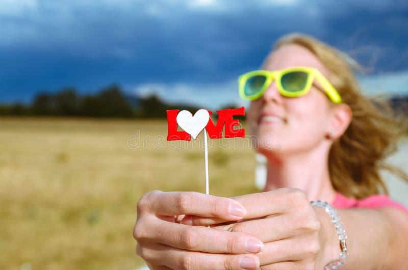Slutet av hållande förälskelsebokstäver för den kvinnliga handen undertecknar upp på pinnen royaltyfria foton