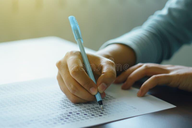 Slutet av handen för student` s rymmer upp en penna skriver på svarsarket Studenten svarar multiplefrågor på trätabellen i examin arkivfoton