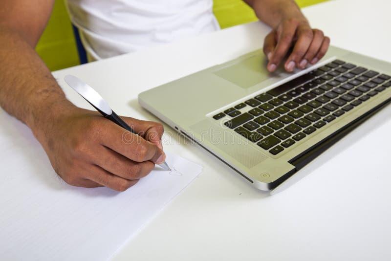 Slutet av indiern mans upp händer som skriver på papper bredvid bärbara datorn arkivfoton