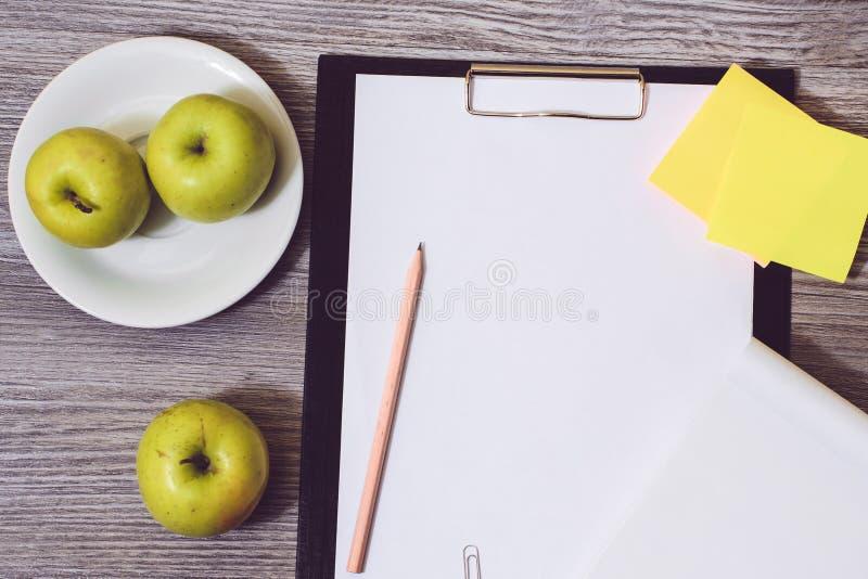 Slutet av kontoret accessorise upp: skrivplatta en platta av äpplen, tom notepad på en träbakgrund Viktförlust som svälter banta  royaltyfri bild