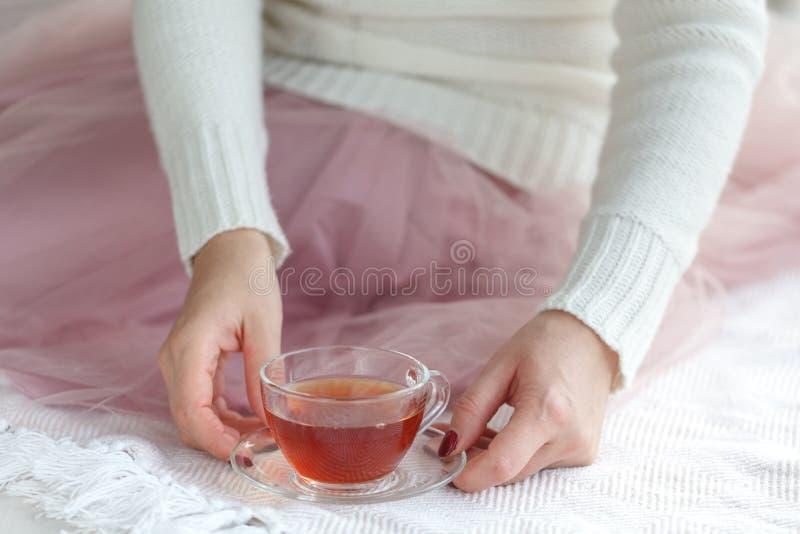 Slutet av kvinna` s räcker upp att rymma en kopp te, att bära en vit tröja och att tycka om fritiden royaltyfria bilder