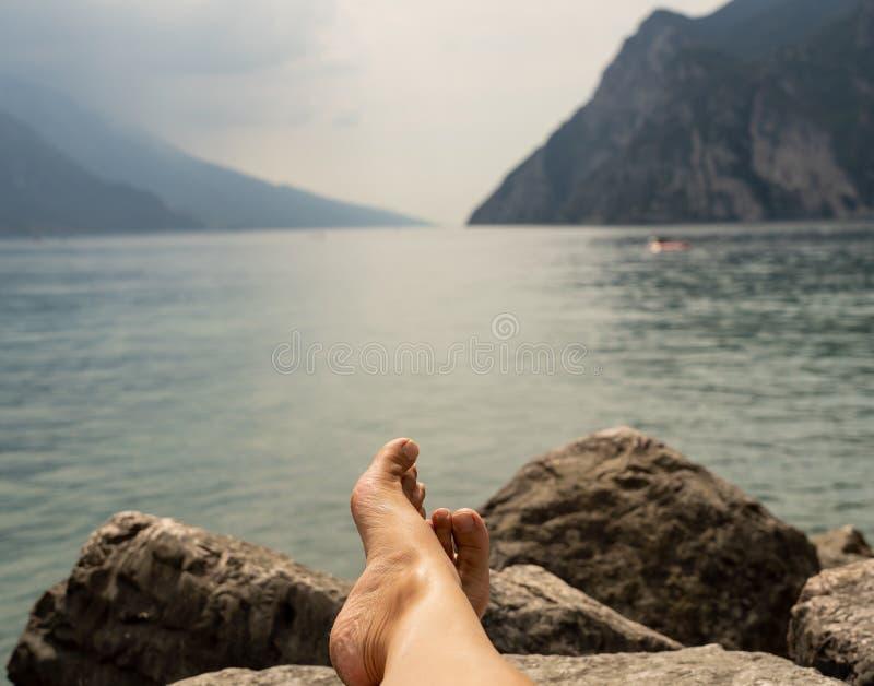 Slutet av kvinnafot som kopplar av av en härlig stor sjö som ligger på kanten av, vaggar upp royaltyfria foton
