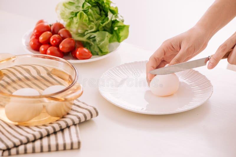 Slutet av kvinnlig räcker upp det klipp kokade ägget för hans frukost a royaltyfri foto