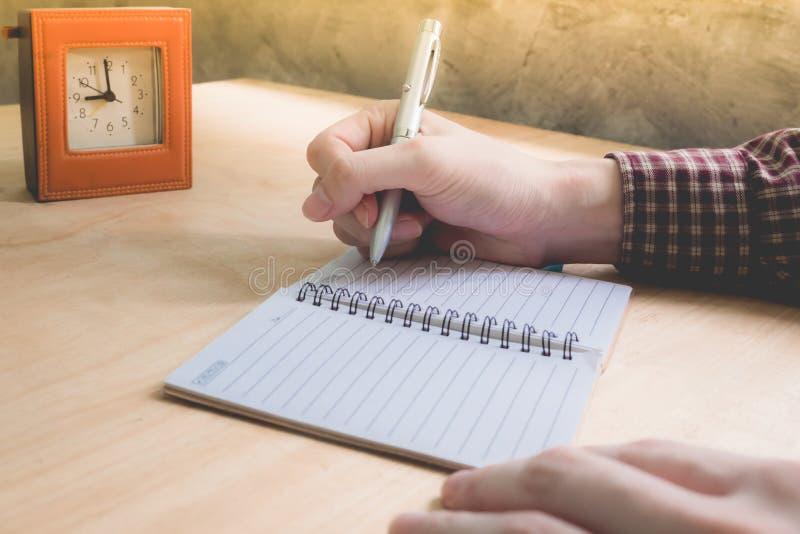 Slutet av mannen räcker upp att skriva några data i anteckningsbok på träskrivbordet arkivbilder