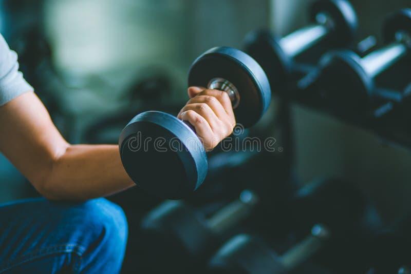 Slutet av passformbarn räcker upp den caucasian stora muskeln i sportswear Hållande hantel för ung man under en övningsgrupp i en fotografering för bildbyråer