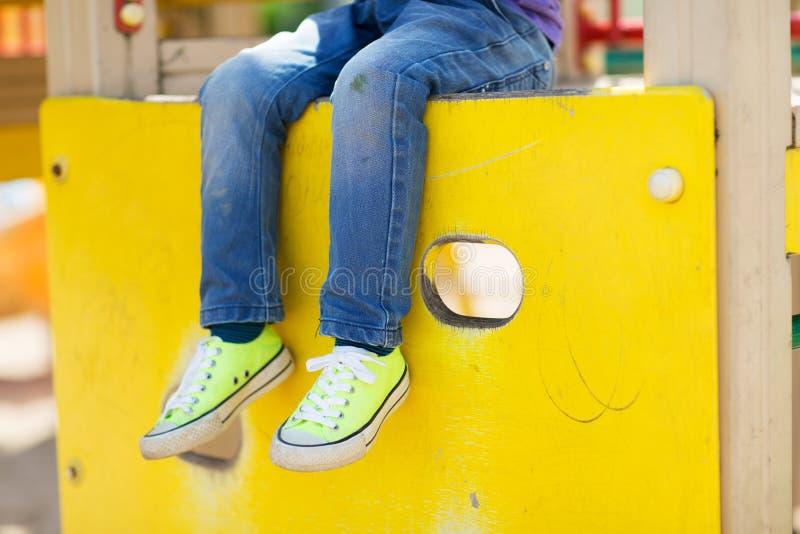 Slutet av pojken lägger benen på ryggen upp på barnlekplats royaltyfri fotografi