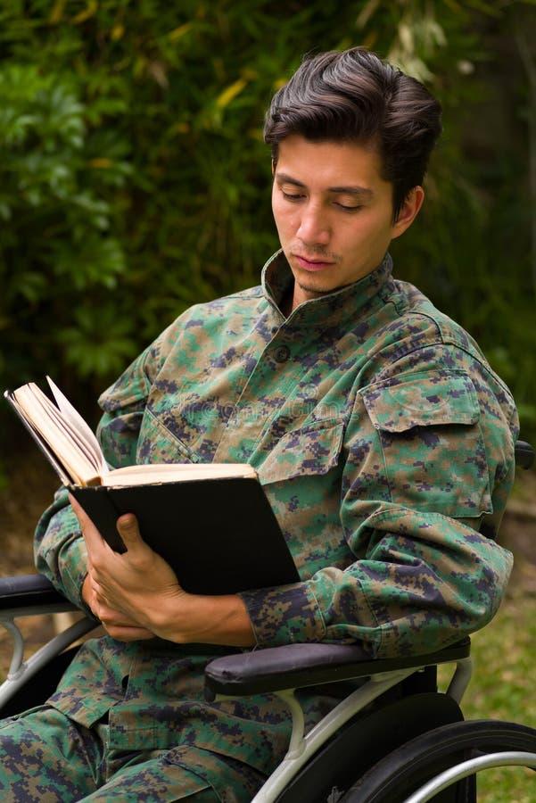 Slutet av stiligt barn tjäna som soldat upp sammanträde på hjulstol som läser en bok i uteplatsen, i en trädgårdbakgrund royaltyfri fotografi