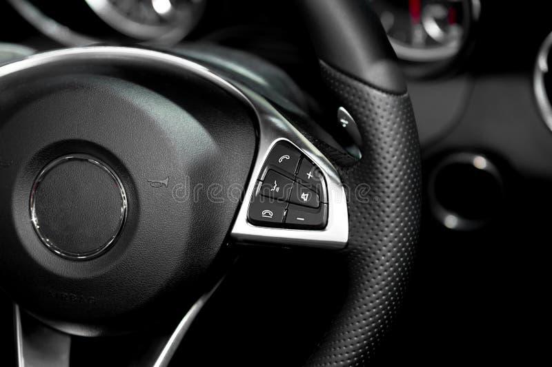 Slutet av styrninghjulet befaller upp i modern lyxig bil Interi royaltyfri bild