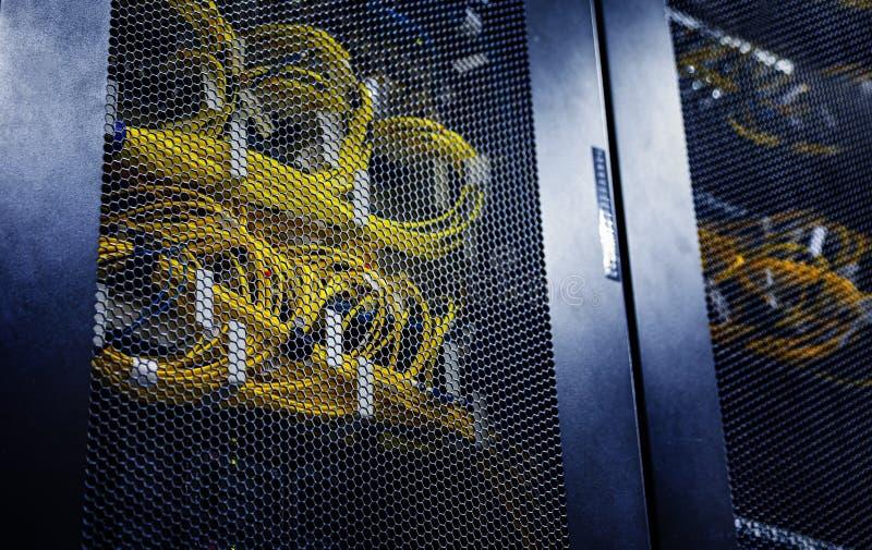 Slutet förband upp gul optisk kabel i kontrollenheter värmer makt Datorserveror i stor datacenter r arkivbilder