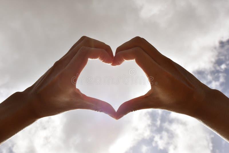 Slutet räcker upp att bilda hjärtan och himlen arkivfoto