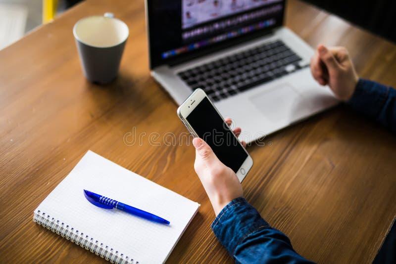 Slutet räcker upp multitaskingmannen som använder bärbar dator- och mobiltelefonförbindande wifi fotografering för bildbyråer