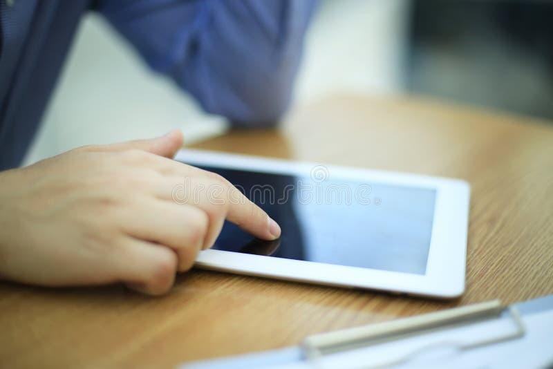 Slutet räcker upp multitaskingmannen som använder minnestavlan, bärbar datorförbindande wifi royaltyfria foton