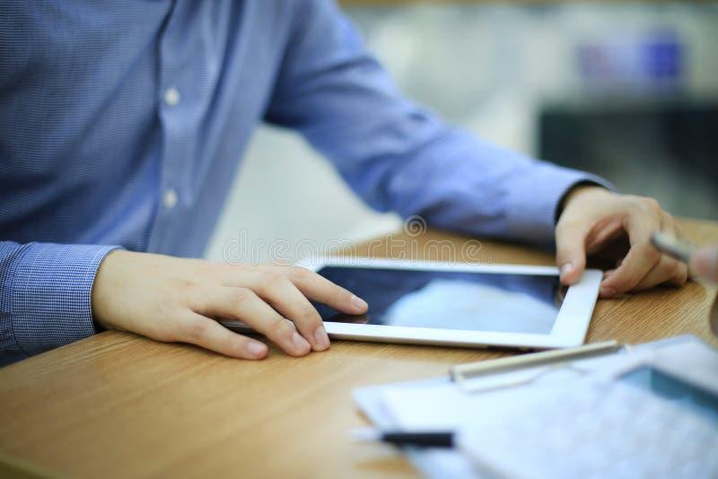 Slutet räcker upp multitaskingmannen som använder minnestavlan, bärbar datorförbindande wifi royaltyfri bild