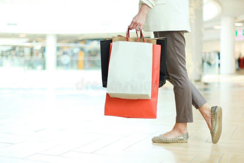 Slutet sköt upp av benet för den unga kvinnan som bär färgrika shoppingpåsar, medan gå i shoppinggalleria royaltyfri fotografi