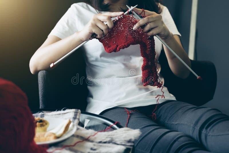 Slutet sköt upp av händer för den unga kvinnan som sticker en röd halsdukhandicra royaltyfri fotografi