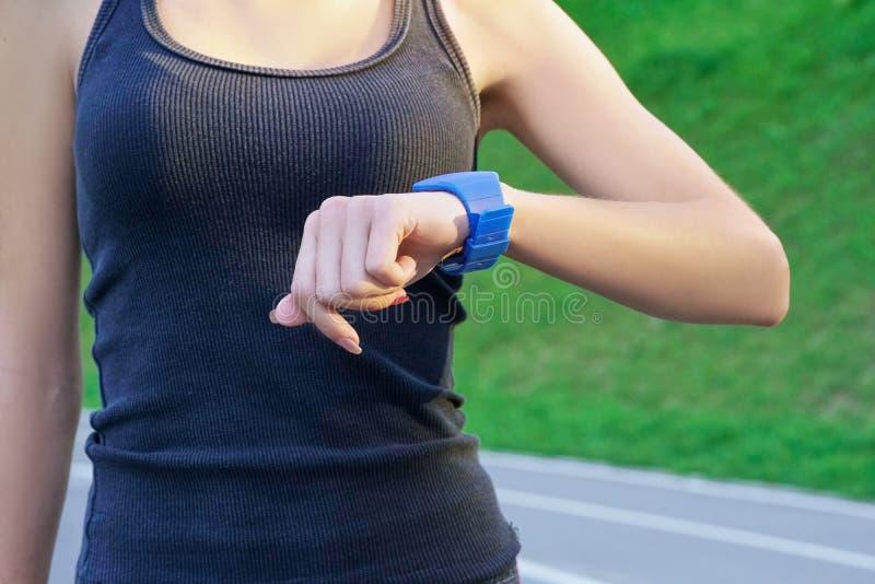 Slutet sköt upp av joggeren för den unga kvinnan som var klar att köra att se smartwatch royaltyfri foto