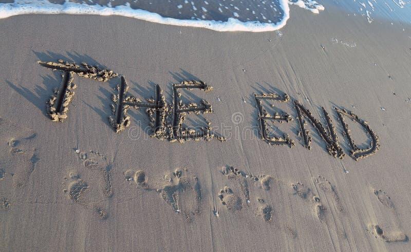 SLUTET som är skriftligt på stranden, medan vågen kommer royaltyfria bilder