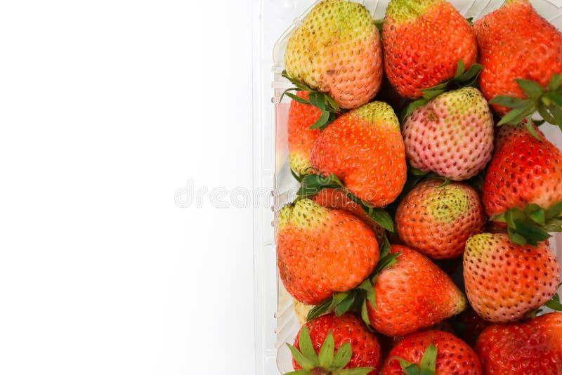 Slutet upp överkant-sikt nära den mogna röda jordgubben i den plast- stordiapacken som isoleras på vit bakgrund, kopieringsutrymm arkivfoton
