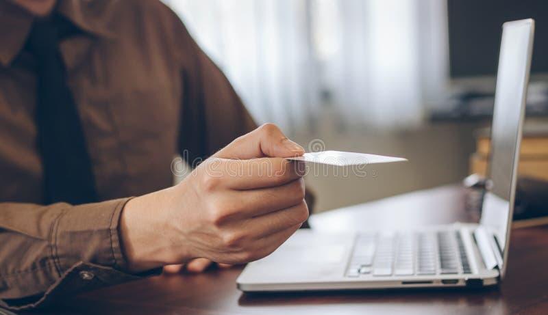 Slutet upp affärsman ger affärskortet för kund med bärbara datorn royaltyfri bild