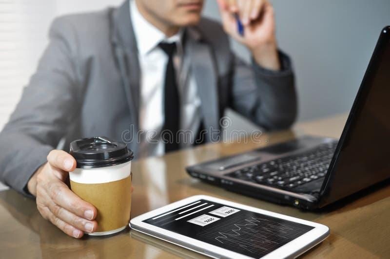 Slutet upp asiatisk affärsman i grå färger passar den hållande koppen kaffe M fotografering för bildbyråer