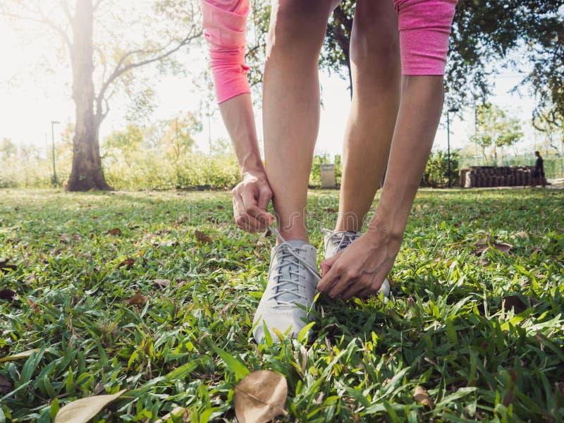 Slutet upp av den unga kvinnan snör åt upp hennes sko som är klar till genomköraren på att öva i parkera med varmt ljust solsken  royaltyfria bilder