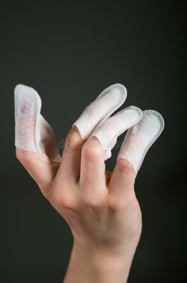 Slutet upp av den unga kvinnan som att bära spikar beskyddandet i henne, spikar, handen och ren manikyr för ideal, i en svart bak arkivfoto