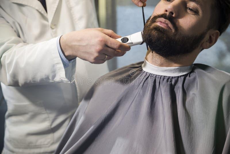 Slutet upp av en allvarlig brun haired affärsman som har hans skägg att kammas och klippas i en barberare, shoppar arkivbilder