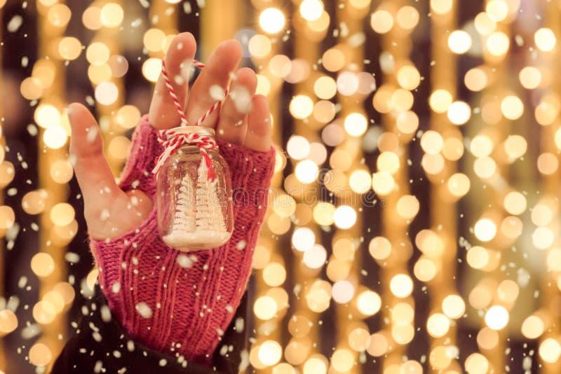 Slutet upp av hållande jul för handen smyckar utomhus med snö f royaltyfria foton