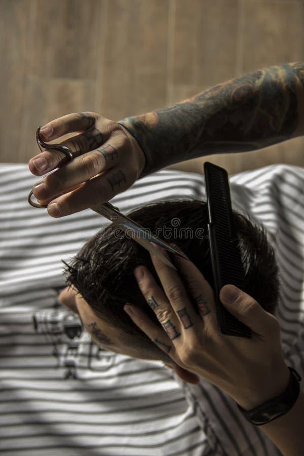 Slutet upp av hairstylingen för man` s och haircutting i en barberare shoppar royaltyfri bild
