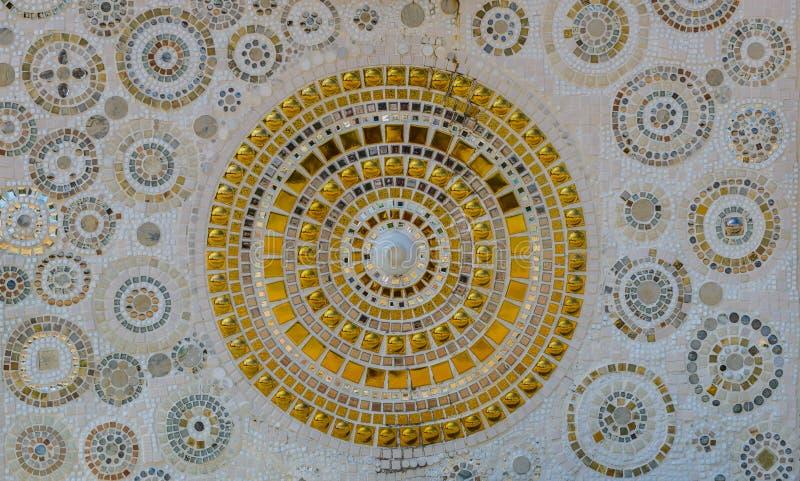 Slutet upp bakgrund av handwork på utsmyckat vitt och keramisk guld dekorerade väggen av buddhismpagoden i Wat Pha Son Kaew, fotografering för bildbyråer