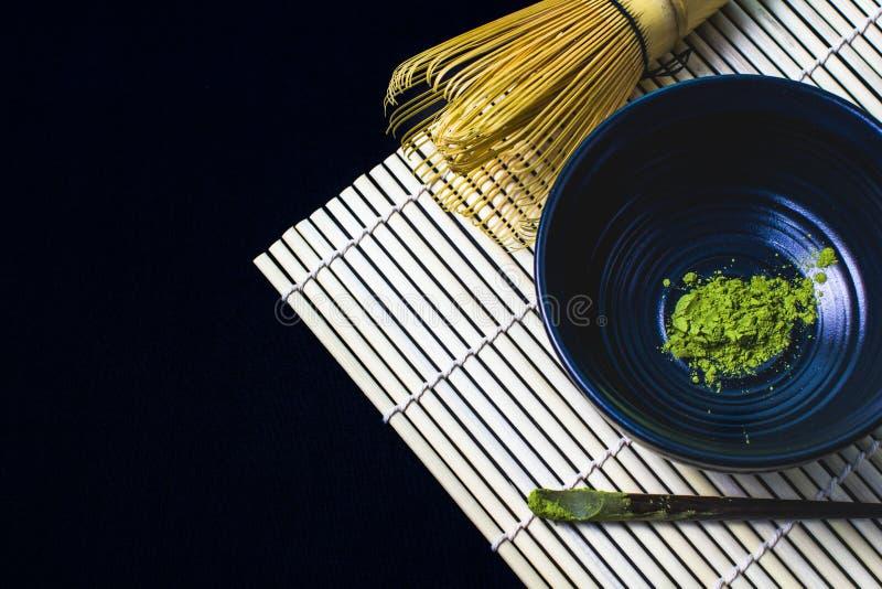 Slutet upp bambu viftar och pulver för grönt te för matcha på svart arkivfoton
