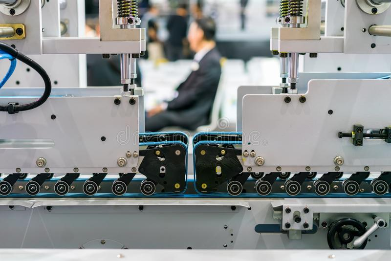 Slutet upp blåa bälten matar hjulenheten av tekniskt avancerat och automatiskt modernt av maskinen för den pappersasken eller låd royaltyfria foton