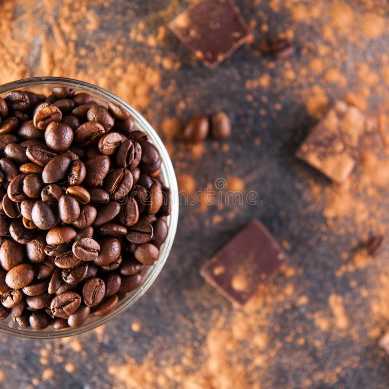 Slutet upp delen av den fulla glass koppen av Roasted kaffebönor på den mörka stenbakgrunden med skingrar kakao, stycken av chokl arkivfoto